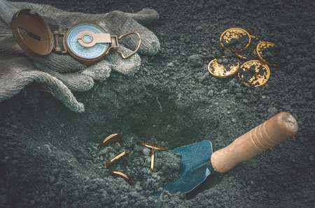Coins searching. Treasure hunting concept. In search of a lost treasure. Imagens