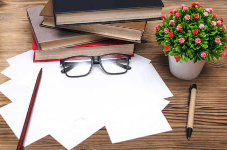 Blank exam tickets, books, school pointer, glasses and a pen on the school desk in the classroom. Education background. Time to test work.