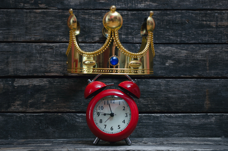 Time to be a leader concept. Coronation or award ceremony time. Red alarm clock under a golden king crown.