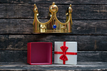 Open present box with copy space on the table with golden king crown above. Royal gift concept.