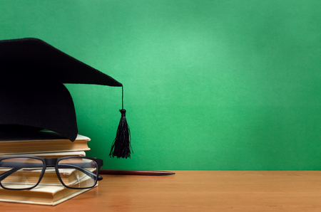 Stack of books, glasses and graduation cap on green school board background. Back to school. Stock Photo