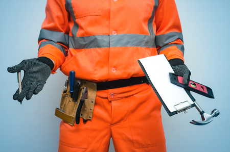 Builder worker is spreading his hands with project plans for measuring results in one hand and with pen in another isolated on blue background. Stock Photo