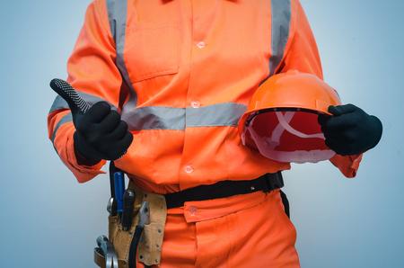 Trabajador de la construcción constructor sosteniendo en la mano un casco y mostrando un pulgar hacia arriba. Concepto de seguridad en el trabajo. Buen trabajo. Foto de archivo