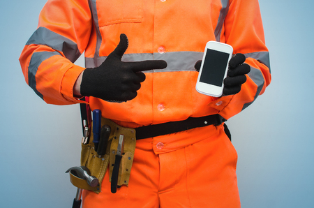 Builder worker is holding in hand a blank screen mobile phone. Call to a repair man concept. Contact us.