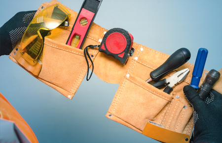 Construction belt with work tools in the worker hands isolated on blue background.