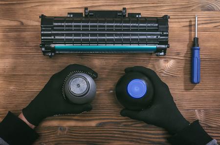 Computer technician engineer is refilling a laser toner cartridge. Office equipment maintenance concept. Reklamní fotografie