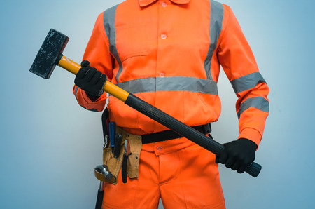 Builder worker holding in hands a big sledgehammer isolated on blue background. Under construction concept.