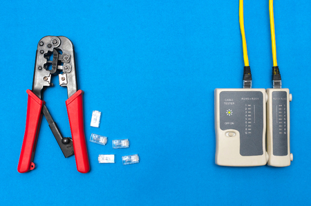 Cripmer tool and network cable tester isolated on the blue background. Network maitenance background with copy space.
