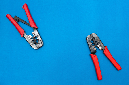 Crimper tool isolated on blue background with copy space. Network maintenance background with copy space. Stock Photo