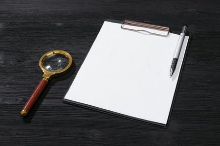 Blank paper page, pen and magnifying glass on the black table background. Searching form. Contract or agreement details. 免版税图像