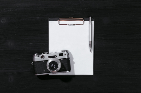 Shot list mockup. Photo session contract template. Vintage film photo camera and blank paper page on black wooden table background. Flat lay design. 스톡 콘텐츠