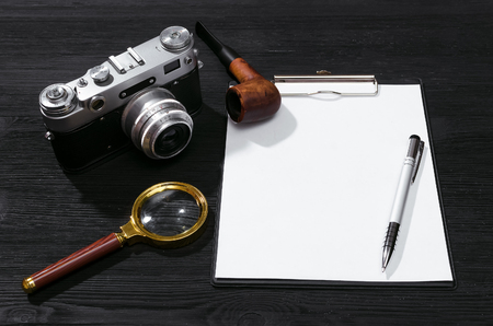 Blank page, pen, film photo camera, magnifying glass and smoking pipe on a black detective agent table background. Top view photo. Secret document mock up. Detective agent report.