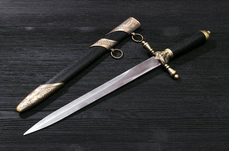 Dagger knife isolated on the black wooden background. 免版税图像