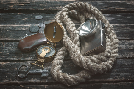 Compass, wallet, coins, rope, flashlight and a key of treasure chest on aged wooden adventurer or treasure hunter table background.