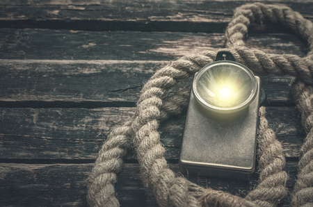 Rope and retro flashlight on the wooden table surface background. Adventurer or treasure hunter desk. Stock Photo