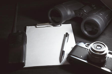 Blank page with copy space, pen, portable radio, binoculars and photo camera on a black spy agent table background. Top secret documents. Detective agent dossier. Interrogation report. 版權商用圖片