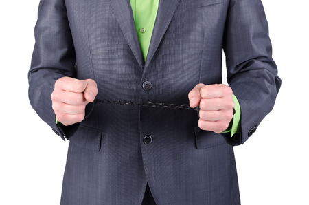 Handcuffs on a businessman hands isolated on a white background. Stock Photo - 114941234