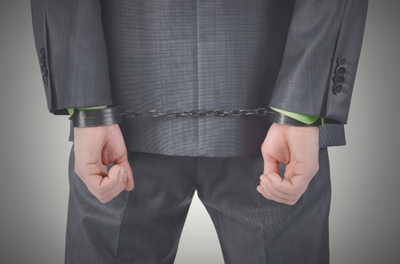 Handcuffs on a businessman hands behind his back isolated on a gray background.