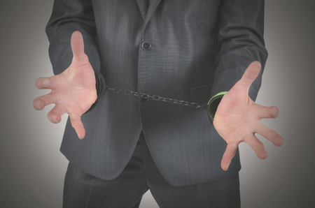 Handcuffs on a businessman hands isolated on a gray background.