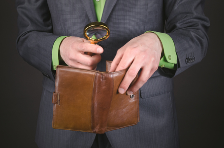 Businessman is looking for money in his empty waller with magnifying glass in his hand to pay the bills. Debts. Low wages. Not enough money.