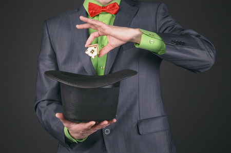 The businessman magician is take out from his hat a small toy house on a black background. Real estate agent. Win a home.