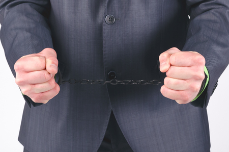 Handcuffs on a businessman hands isolated on a white background.
