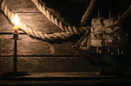 Ship, mooring rope and burning candle on the wooden table. Sea travel concept background. Pirate. Reklamní fotografie