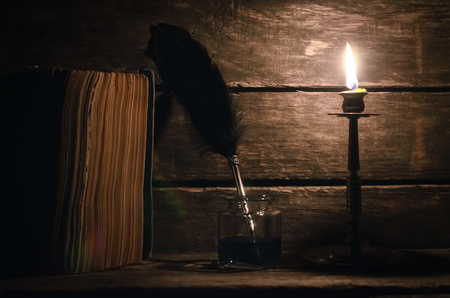 Quill pen in a inkpot and book in the light of burning candle on the writer desk background. Education concept.