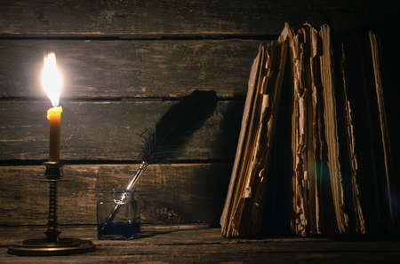 Quill pen in a inkpot and stack of books in the light of burning candle on the writer desk background. Education concept. Standard-Bild
