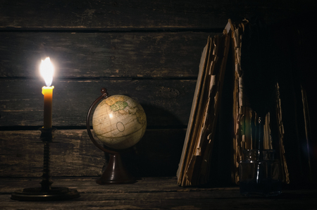 Quill pen in a inkpot, globe and stack of books in the light of burning candle on the writer desk background. Education concept or traveler diary.