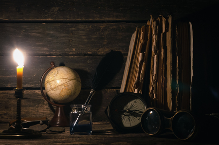 Travel or adventure concept background. Compass, binoculars, globe map, stack of books, quill pen on the adventurer table.