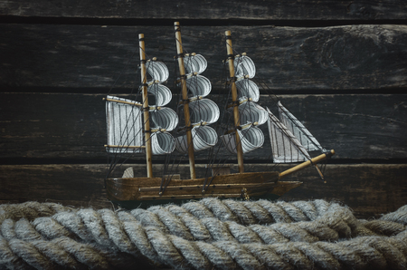Sailboat and mooring rope on a wooden captain table background. Sea travel concept. Reklamní fotografie