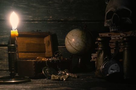 Pirate treasure chest with a gold on a pirate captain table in the light of burning candle background.