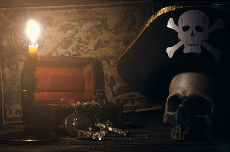 Pirate map and treasure chest with a gold and human skull in captain hat on a pirate captain table in the light of burning candle background.