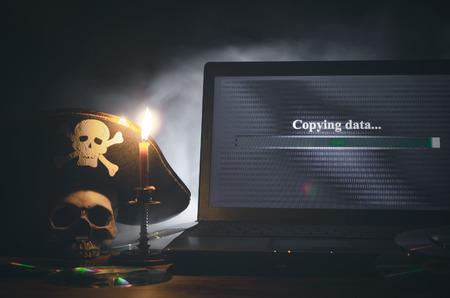 Concept de copie de données illégale. Cybercriminalité. Contexte de piratage informatique. Chapeau de pirate, crâne humain, ordinateur portable et disque compact sur une table.