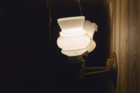 Retro style wall lantern switched on in the dark room of living room background.