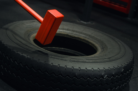 Red hammer and a tyre in the gym. Strength training.