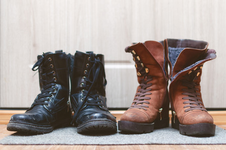 Female suede brown shoes and worn out male black leather boots on the floor in a hallway. Stockfoto