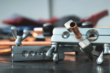 Pipe rammer tool on a fitter workbench. Pipework concept background. Stock Photo - 117381793