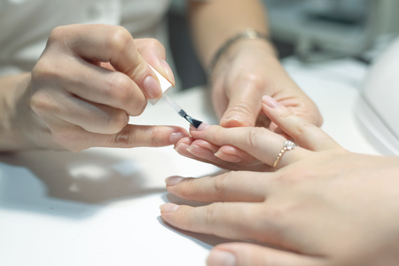 Manicurist is applying a nail base gel on a female finger nails. Nail care concept.
