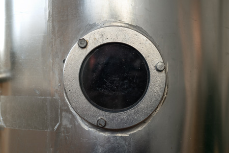 Transparante patrijspoort (bulleye) op een zilveren muurtankachtergrond. Stockfoto