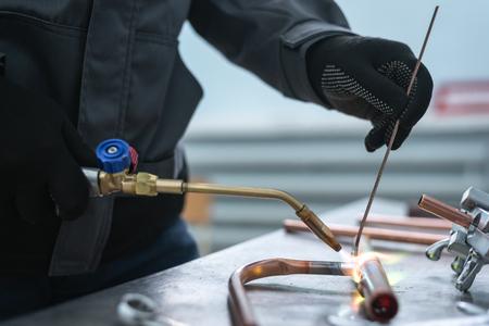 Werknemer soldeert een pijp door een blaaslamp op de achtergrond van een fabriekswerkbank. Leidingwerk. Stockfoto