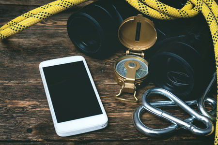 Blank screen mobile phone, carabiners, compass, safety rope and binoculars on a brown wooden board background with copy space.