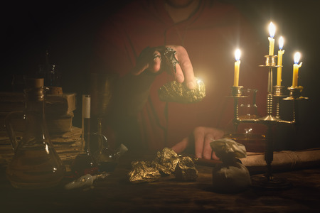 Alchemist is working at his magic table and producing a gold from a stones. Imagens - 117467790