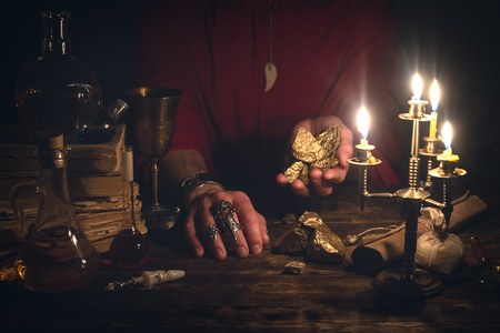 Alchemist is working at his magic table and producing a gold from a stones. Imagens - 117467835