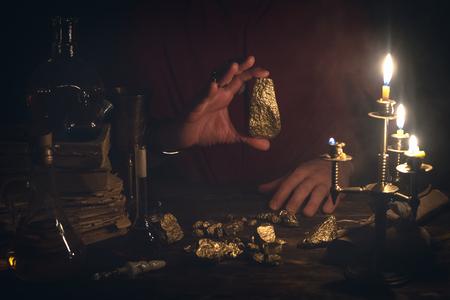El alquimista está trabajando en su mesa mágica y produciendo un oro a partir de piedras.
