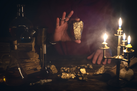 Alchemist is working at his magic table and producing a gold from a stones.