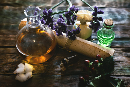 Herbal medicine essential oil and various herbs on a table and ancient recipe scroll. Witchcraft. Banque d'images - 117468083