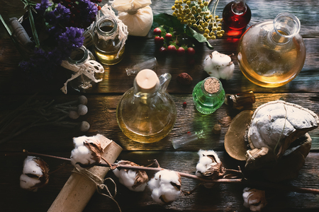 Herbal medicine essential oil and various dry herb on a table. Witchcraft. Witch doctor concept background. 写真素材