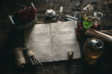 Ancient recipe scroll book and various dry herbs on a table of witch doctor. Herbal medicine essential oil on a table. Witchcraft background with copy space. Фото со стока